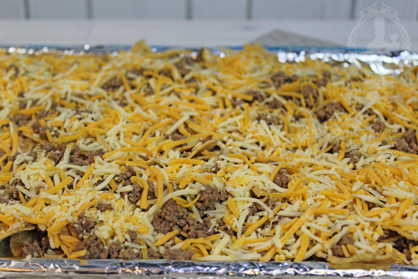 Cheese added on top of layer of chips and ground beef.