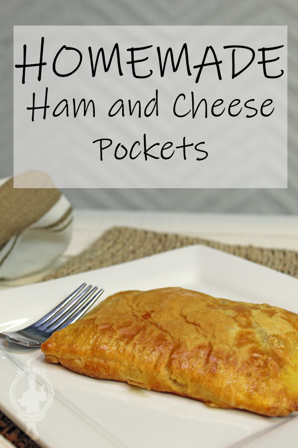 A ham and cheese pocket on a white plate with a fork ready to cut into it.