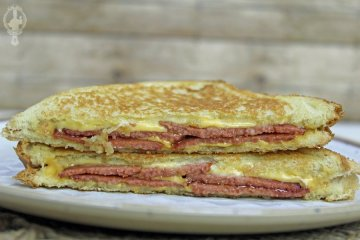 Two halves of the fried bologna grilled cheese stacked on each other.