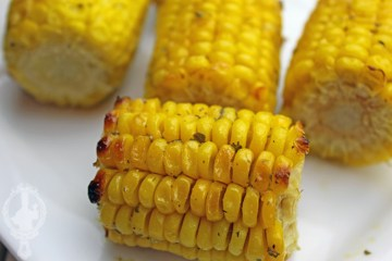 Close up of a serving plate of baked corn on the cob, ranch style.