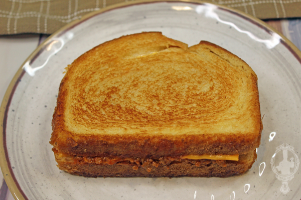 Half of the Sloppy Joe Grilled Cheese Sandwich is cooked on a plate.