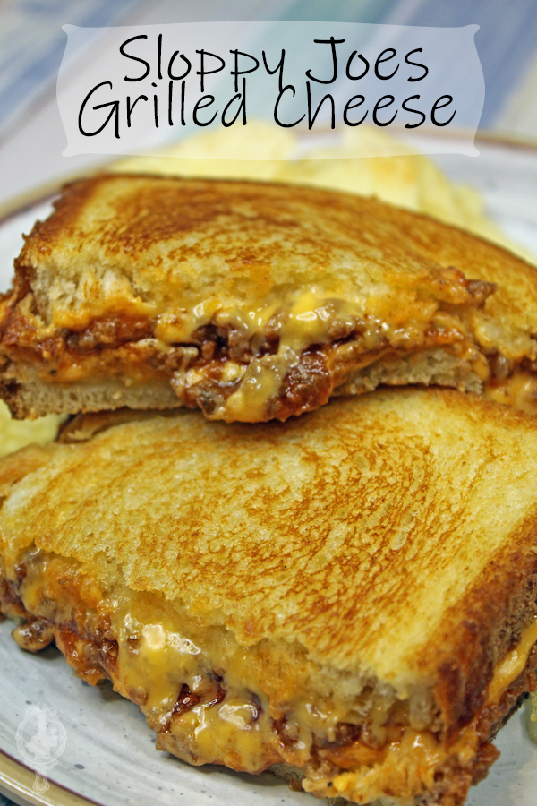 Two halves of a Sloppy Joe Grilled Cheese with potato chips in the background.