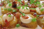 Close up of twice baked sliced potatoes on a serving plate.