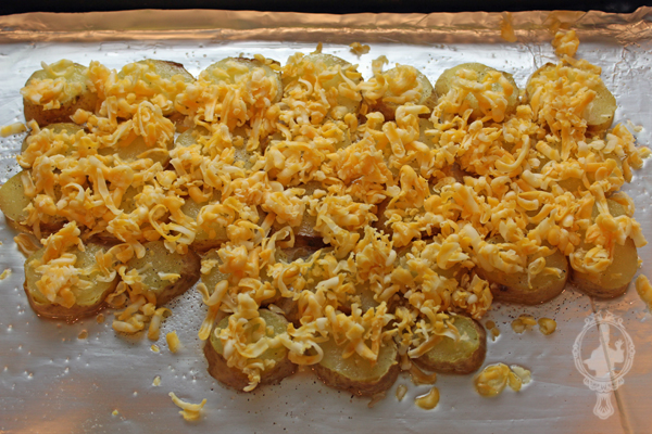 Sliced potatoes on a baking sheet with shredded cheese sprinkled on top of them.
