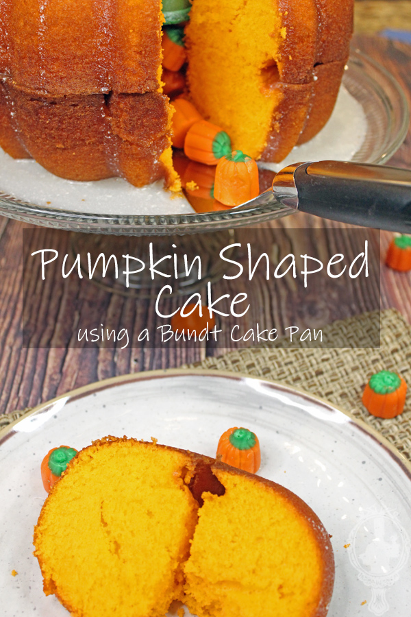A slice of pumpkin shaped bread on a plate.  The pumpkin shaped cake on a cake stand in the background.