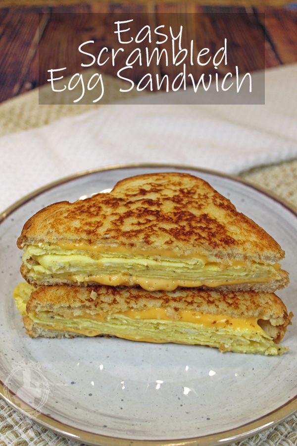 Two halves of a scrambled egg sandwich on top of each other.