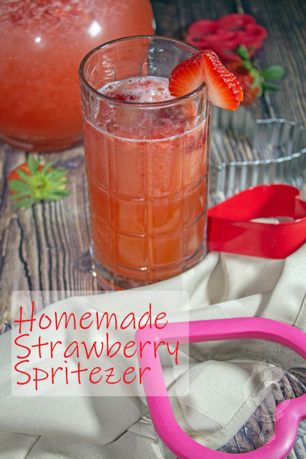 A glass and pitcher with Strawberry Spritezer in them.