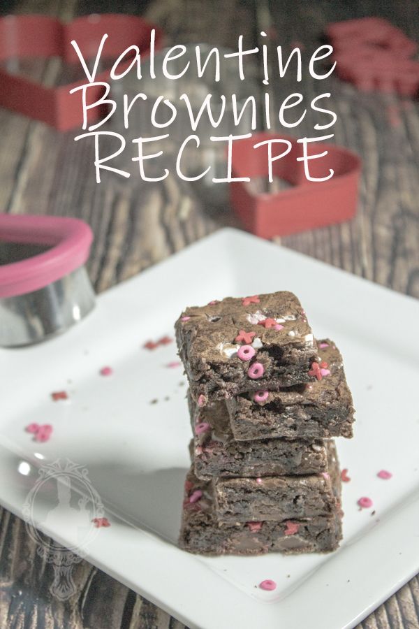 A stack of 5 brownies on a white plate.
