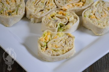 A plate with some sliced chicken salad pinwheels, ready to eat.