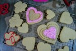 Overhead view of cut out soft sugar cookies on a rack with a couple frosted.