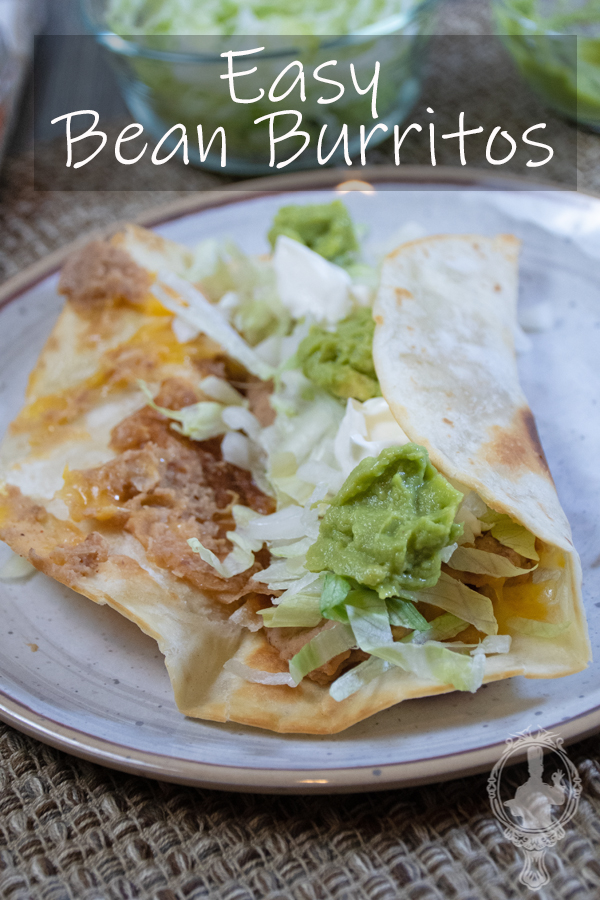 An open bean burrito on a plate with lettuce, guacamole and sour cream on top.