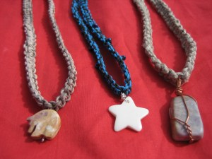 From left to right: stone bear, bone star, polished rock necklaces.