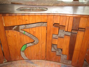This is the sink area in the kitchen. The doors to the cabinets under the sink are made of wood with cut out designs.