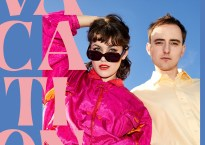"Man and woman in pink and beige clothing against light blue background with super imposed large pink text that reads ""Vacations"""
