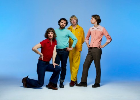 Photo of four people in different colored outfits, against a light blue background