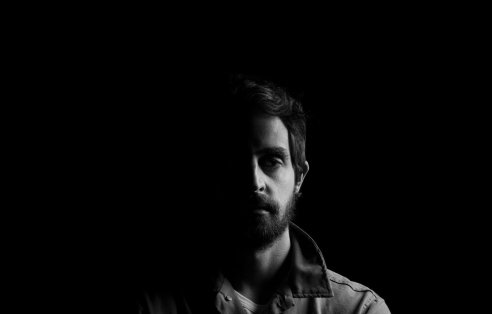 Black and white portrait photo of man against black background