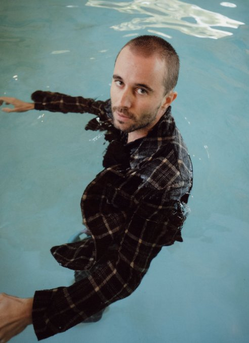 Close up photograph of man in black clothing floating in pool