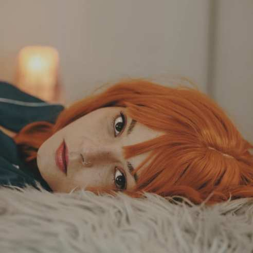 Up close portrait of a woman with bright red hair, laying on her side