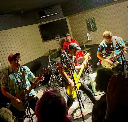 Four men playing musical instruments in front of a crowd. the wall behind the band is light beige. A red board hangs on the wall to right of the band.