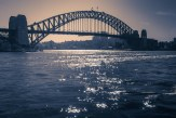The light across the water acts like a path for the eyes, to a point behind the Sydney Harbour Bridge.