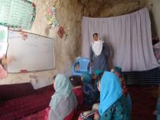 Höhlenschule in Bamian. Die Lehrerin – selbst ein Binnenflüchtling – und ihre Schüler. Foto: Thomas Ruttig