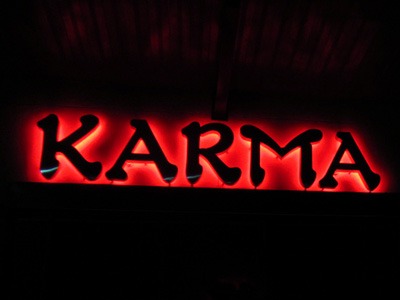 Red neon sign that says 'Karma'.