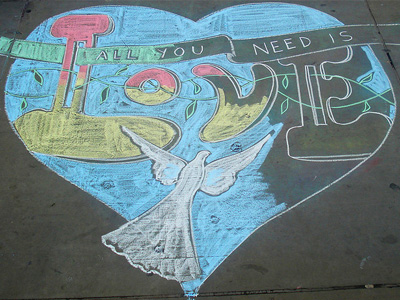 Sidewalk chalk drawing of a heart and the words 'All you need is love.'