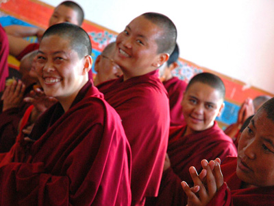 Happy Tibetan Buddhist nuns smiling.