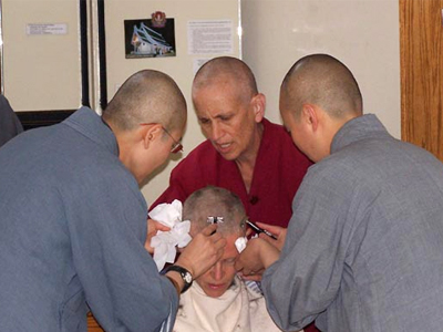 Venerable Tarpa getting her head shaved by Venerable and other monastics.