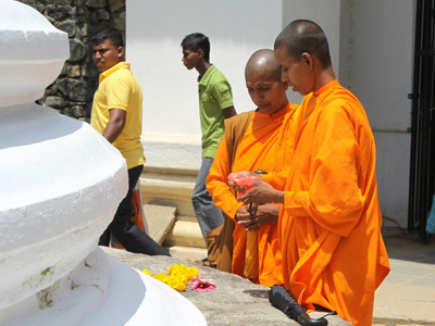 Sri Lankan Buddhist nuns making offerings of flowers at a stupa.