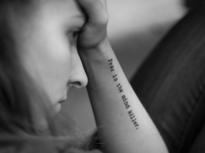 A woman putting her hand on her forehead, the words: Fear is the mind killer on her arm.