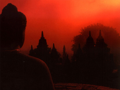 Silhouette of a Buddha statue with bright in front of a fire-red sunset.