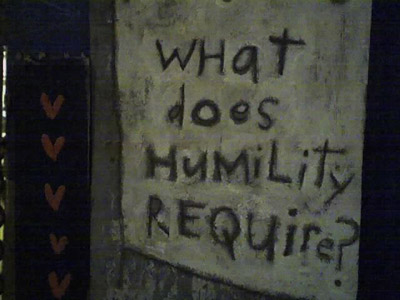 The words: What does Humility require?, written on a wall.