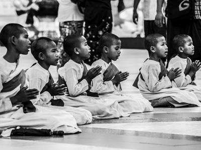 A group of young novice Buddhist nuns in prayer.
