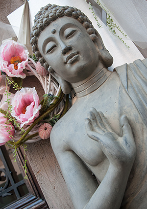 Large Buddha statue with pink flowers in background.