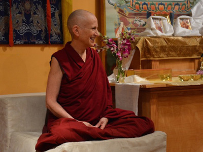 Venerable Thubten Chodron sitting in meditation position and smiling happily.