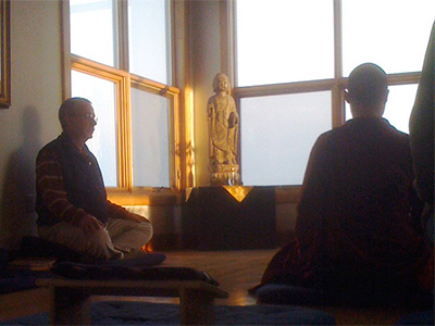 A monastic and lay practitioner meditating together.