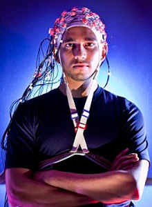 A man wearing a brain cap with alot of wires attached to it.