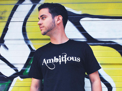 Young man wearing black t-shirt with the word 'Ambitious' on it.