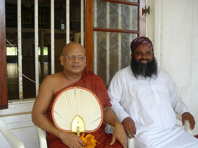 A Buddhist monk and a Muslim priest, sitting together.