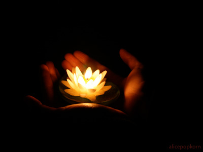 Someone's hand holding a lotus candle with light in a dark place.