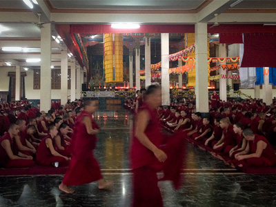 Many monks in a large hall at Drepung Monastery.