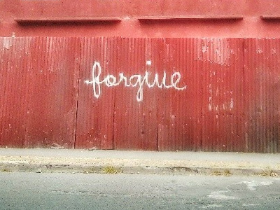The word 'forgive' spray painted on a red wall.