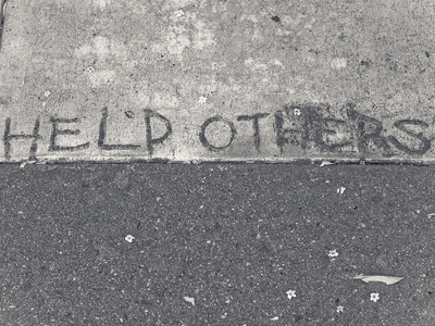 The words 'Help others' written on a concrete sidewalk.