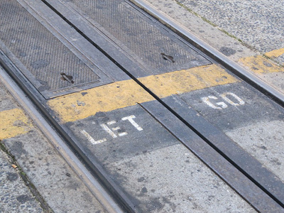 The words 'Let go' painted on cable car tracks.