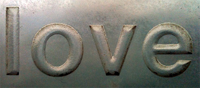 The word 'love' stamped into metal.