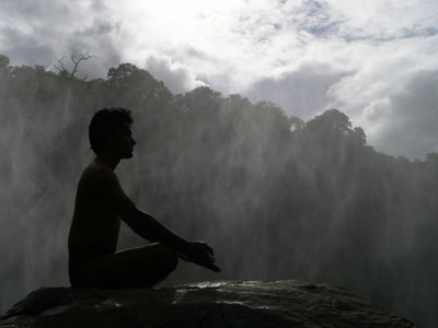 A man sitting on a big rock meditating, huge trees in background.
