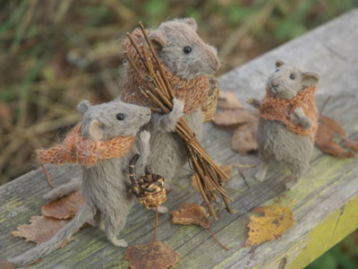 3 stuffed mice-One bigger mice taking sticks, one smaller mice taking a basket and one small mice looking at the big one carrying the sticks.