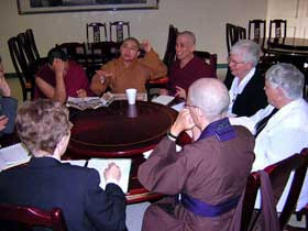 A group of nuns from various religions sitting at a table, talking.