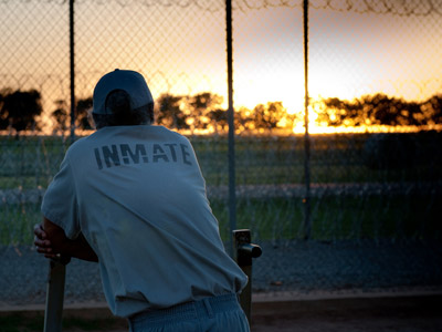 A photo showing an inmate back, looking at the sunset.